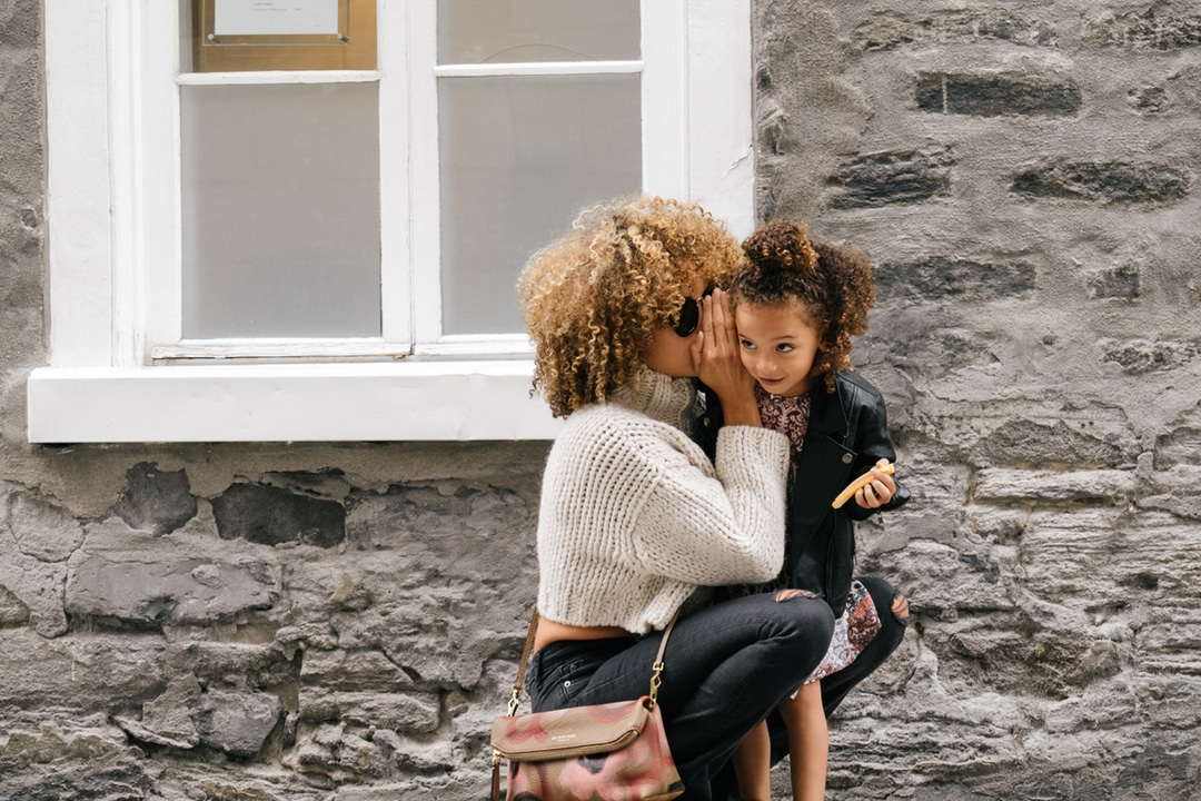 pic of mother whispering to daughter