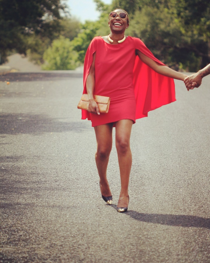 pic of girl laughing and wearing red cape dress blue labels boutique