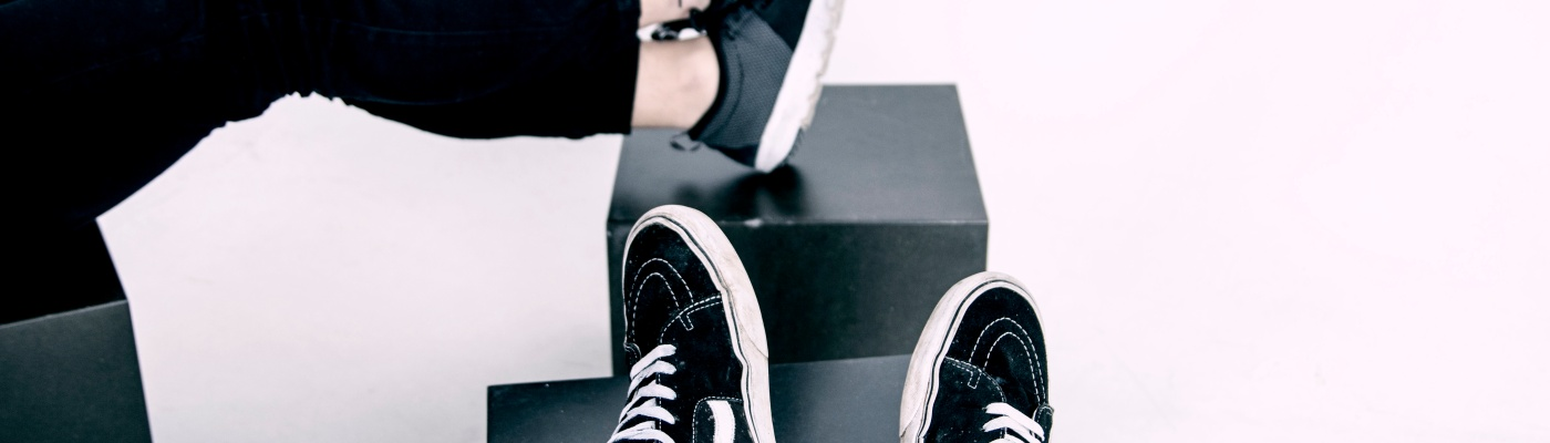 pic of man and women wearing black tennis shoes propped on top of boxes