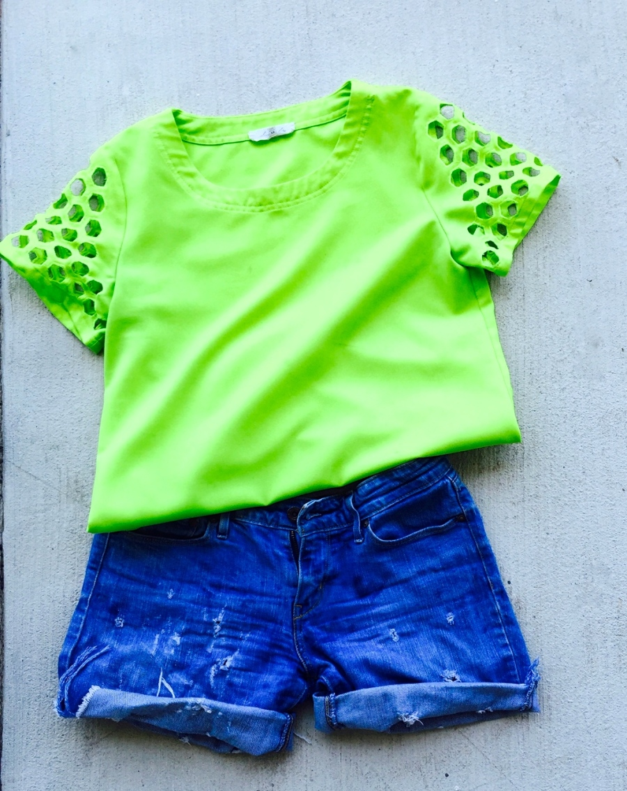 neon green top with cut out holes, denim shorts