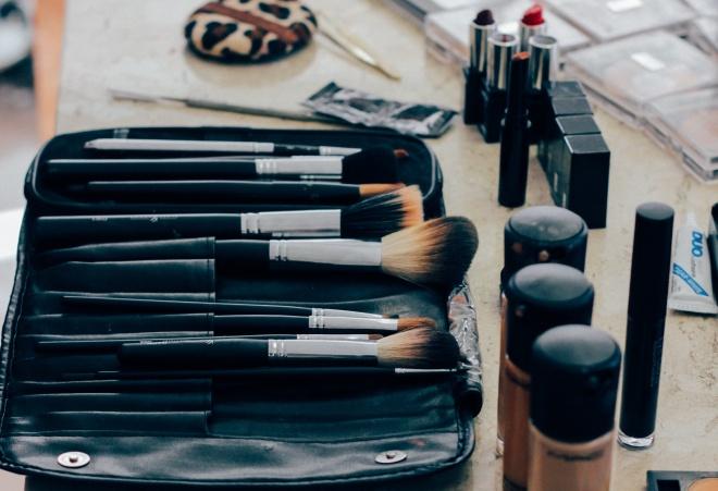 set of make up brushes, lipstick, and foundation