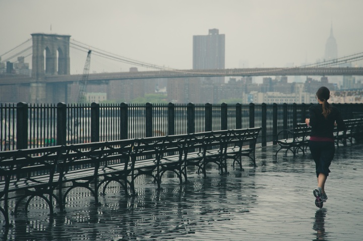 girl running outside by a bridge