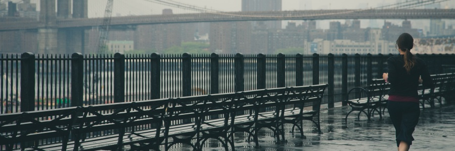 girl running outside by a bridge
