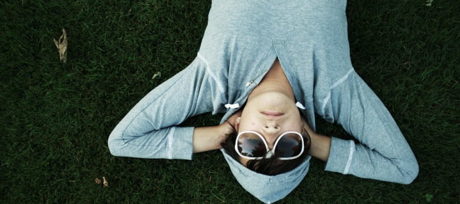 pic of woman lying down wearing sunglasses and hoodie
