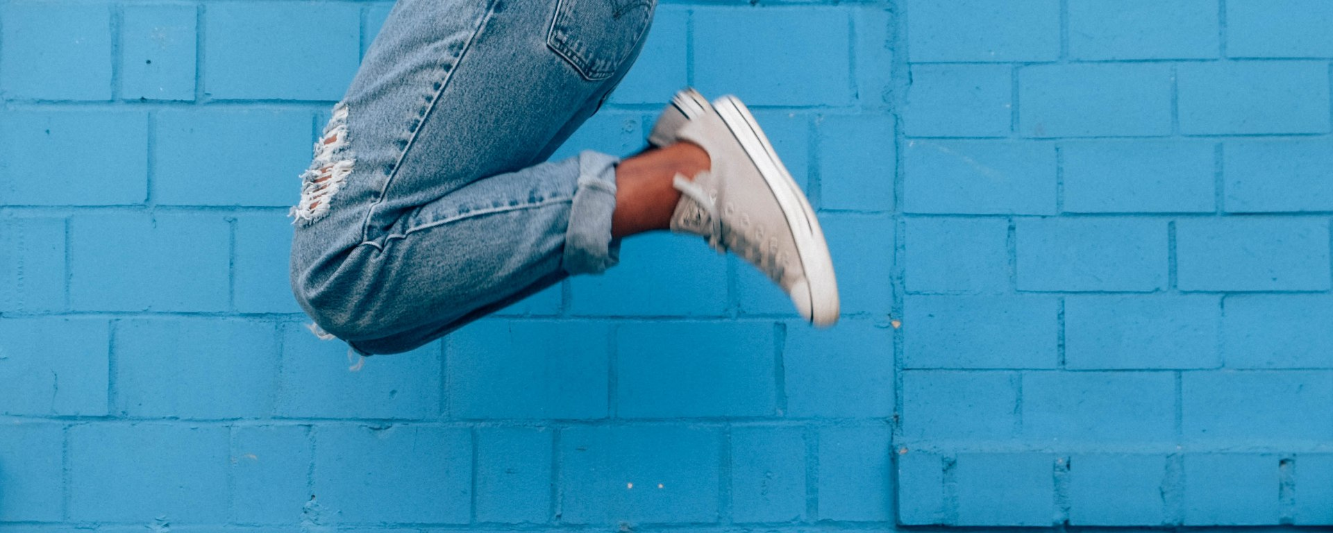 jeans with sneakers jumping in front of blue wall
