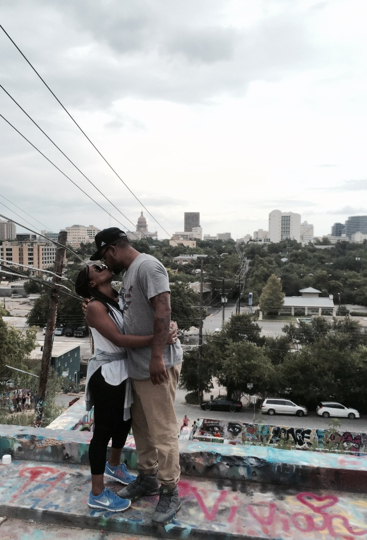 couple kissing on graffiti wall