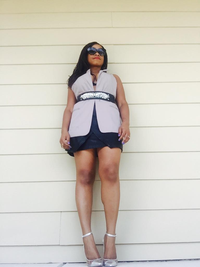 black woman wearing black leather wrap skirt, vest, and belt