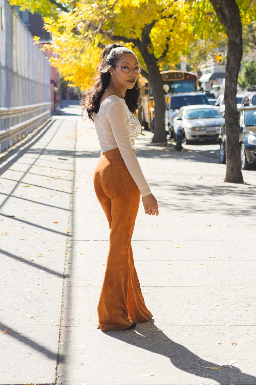 Sade Spence wearing rust colored suede flares and white sheer bodysuit blue labels boutique
