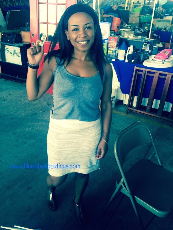 black woman holding money up at vendor show