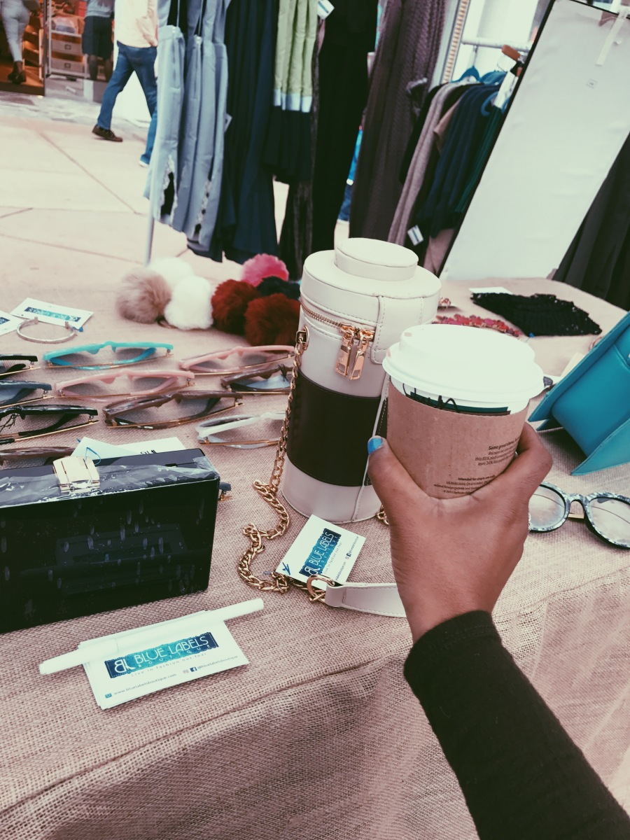 holding coffee at blue labels boutique pop up shop