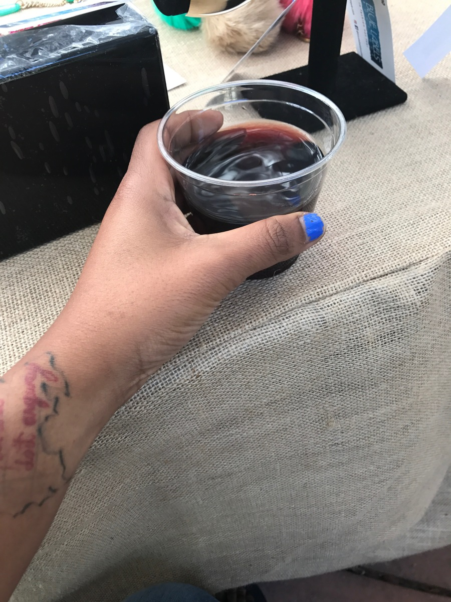 blue labels boutique owner holding a glass of wine