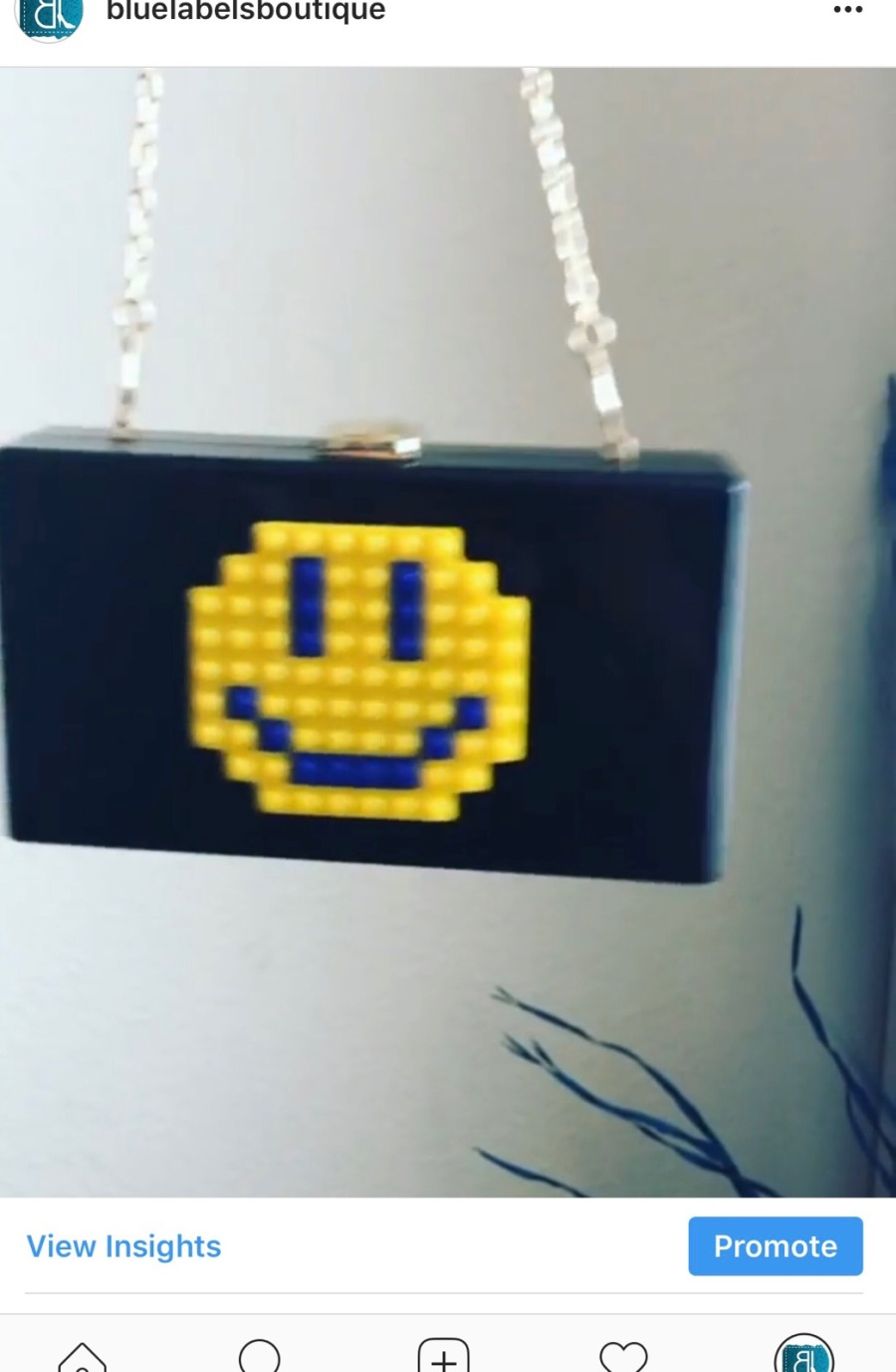 pic of clutch with a smiley face blue labels boutique