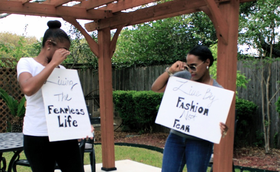 image of two women holding living the fearless life signs fashion not fear