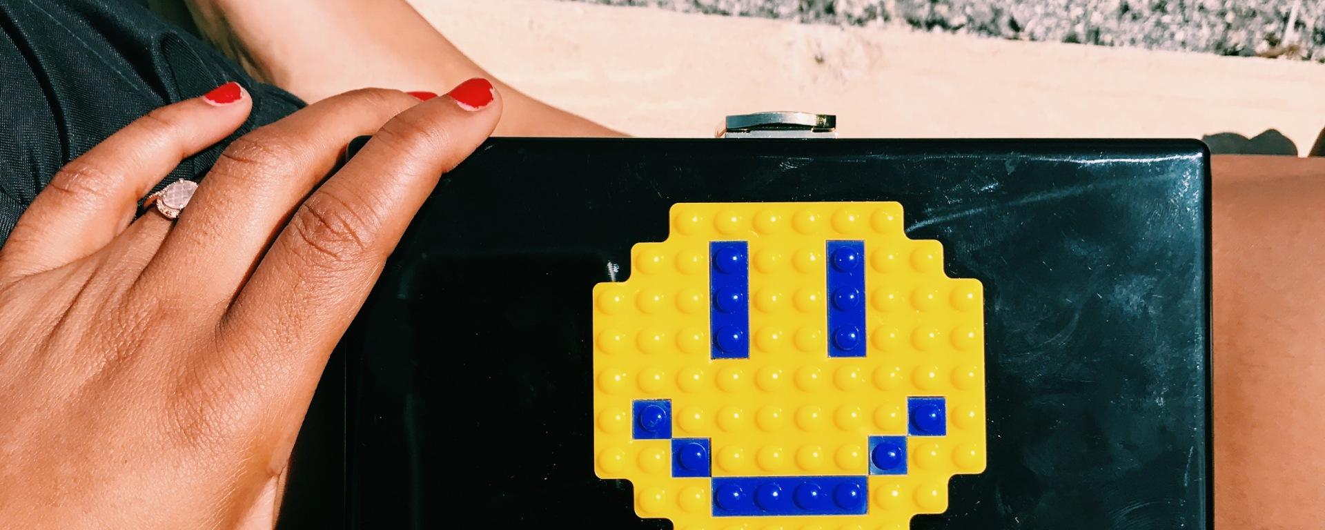 black clutch bag with smiley face blue labels boutique