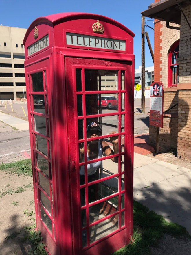 Blue Labels Boutique owner in red phone booth in denver colorado
