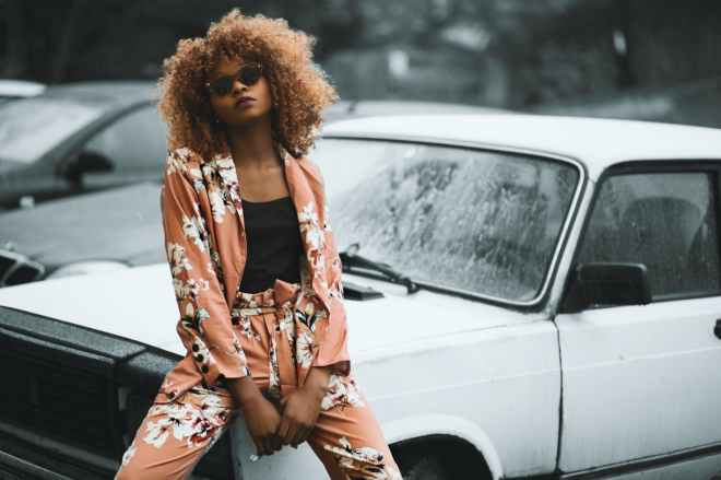 woman wearing brown floral print coat and pants sitting on car