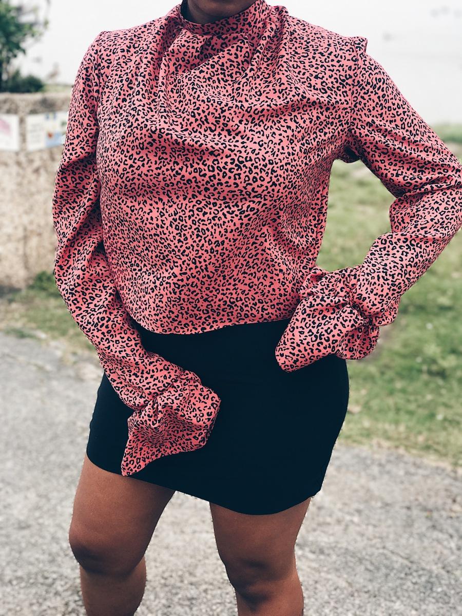 woman wearing pink black animal print blouse